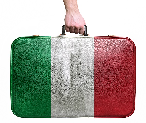 Tourist hand holding vintage leather travel bag with flag of Ita