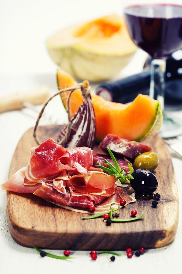 Italian cuisine. Antipasto. Prosciutto, melon, salami, olives and wine