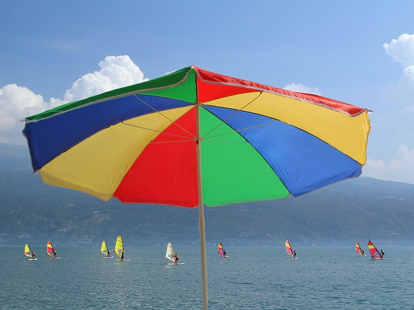 Beach umbrella in rainbow colors and group of windsurfers on gar