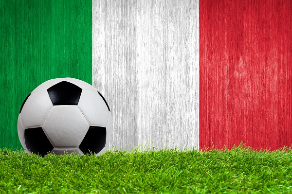 Soccer ball on grass with Italy flag background