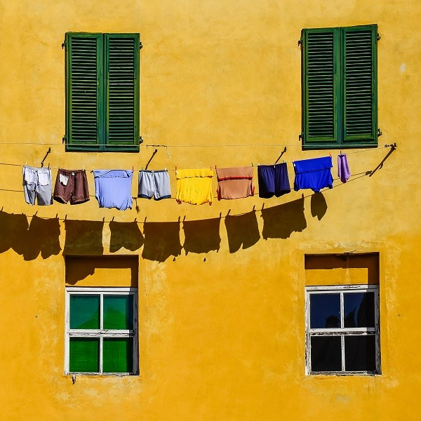 Detail of colorful yellow house walls, windows and clothes