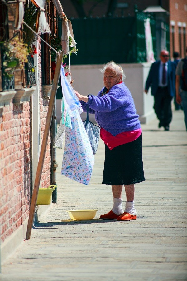 Old woman hanging laundry